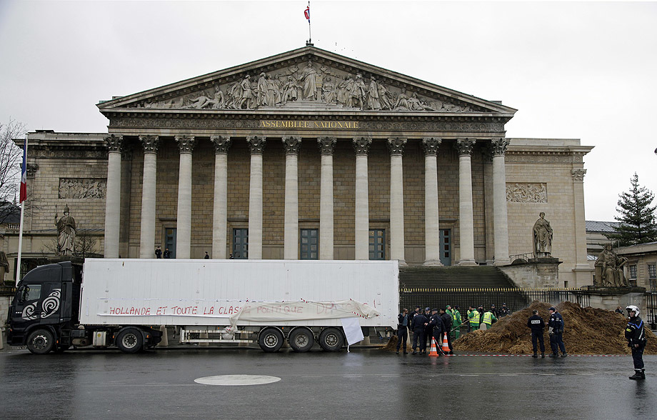 French police stand guard near a lorry that displays a protest banner reading and a large pile of manure in front of the National Assembly in Paris,