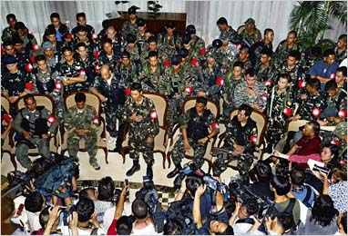 Renegade Philippine soldiers face newsmen inside the Oakwood apartments in Manila's Makati financial district July 27, 2003. Most of the rebel soldiers said they were willing to negotiate with the government to end a stand-off but added they had no immediate plans to surrender.  The Philippine government said a deadline for the mutineers to give themselves up had been extended to 7 p.m. (11 GMT).   REUTERS/Erik de Castro