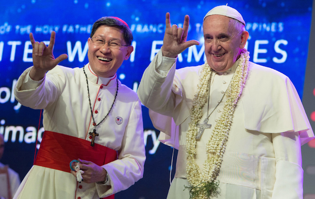 Pope Francis and Manila Archbishop Luis Antonio Tagle salute the crowd with the popular hand sign for