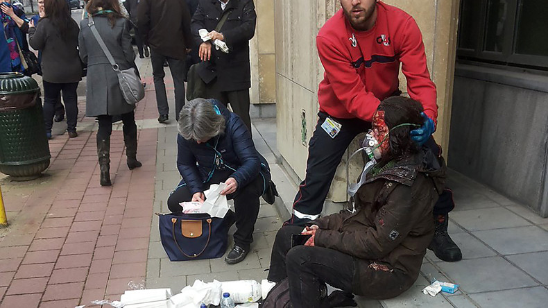 A private security guard helps a wounded women outside the Maalbeek - Maelbeek metro station in Brussels on March 22, 2016 after a blast at this station. © Michael VILLA / AFP