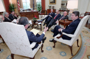 President Reagan meeting with Charles Wick on March 7, 1986, in the Oval Office. Also present: Stephen Rhinesmith, Don Regan, John Poindexter, George Bush, Jack Matlock and Walter Raymond (seated next to Regan on the left side of the photo). (Photo credit: Reagan library)