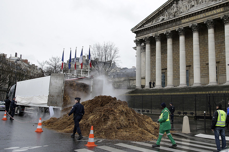 French police an municipal workers walk near a large pile of manure sits in front of the National Assembly in Paris