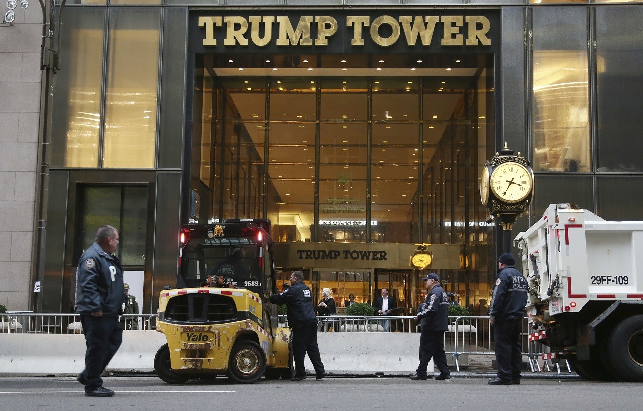 """Police officers help to install concrete barriers around Trump Tower, the home of President-elect Donald Trump, in New York, Wednesday, Nov. 9, 2016. A day after Trump, against all odds, won election as America's 45th president, Hillary Clinton on Wednesday lamented that the nation proved to be """"more divided than we thought"""" but told supporters: """"We owe him an open mind and a chance to lead."""" (AP Photo/Seth Wenig)"""