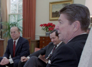 "Walter Raymond Jr., a CIA propaganda and disinformation specialist who oversaw President Reagan's ""perception management"" and psyops projects at the National Security Council. Raymond is partially obscured by President Reagan and is sitting next to National Security Adviser John Poindexter.. (Photo credit: Reagan presidential library)"