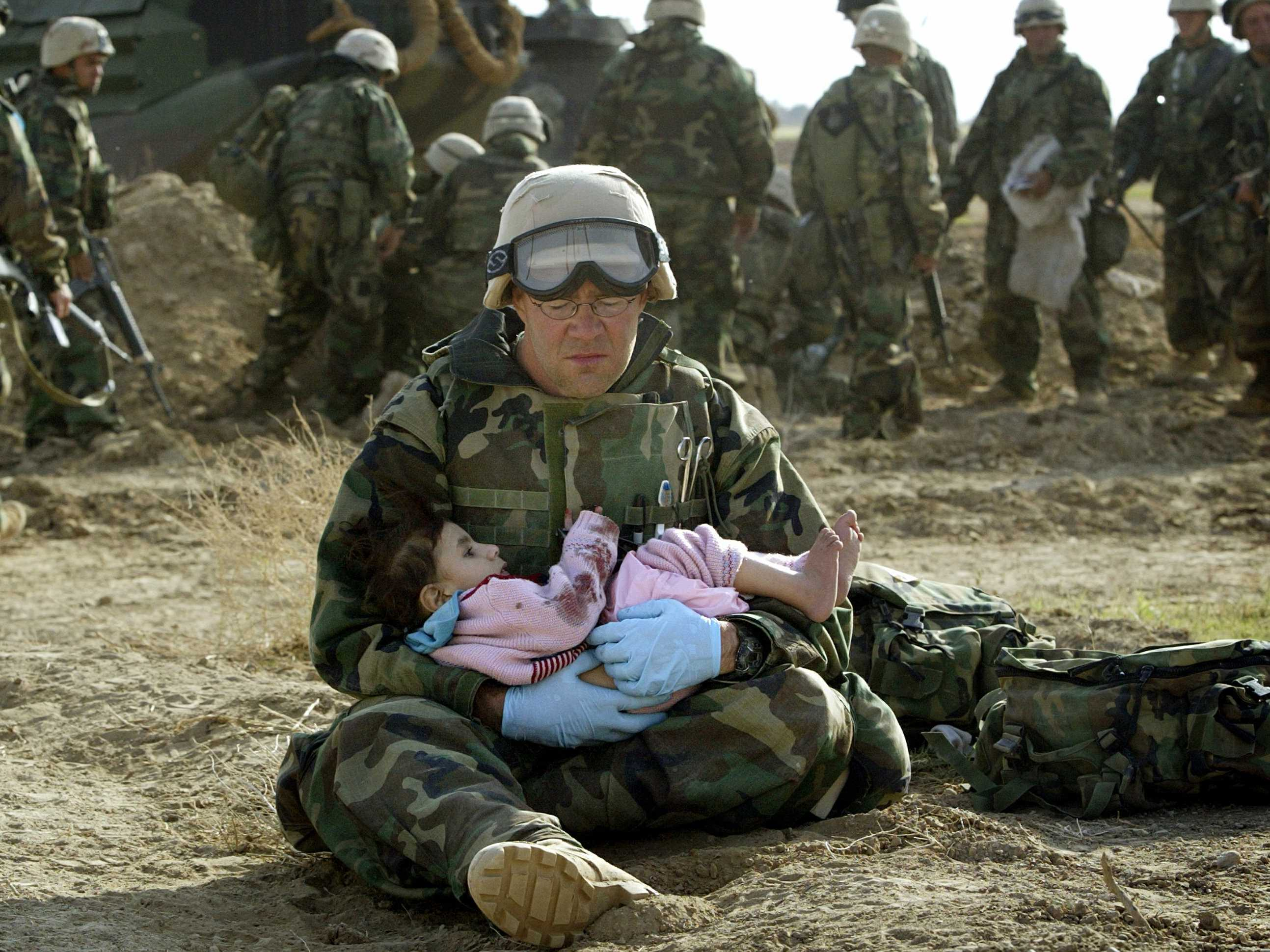 U.S. Navy Hospital Corpsman HM1 Richard Barnett, assigned to the 1st Marine Division, holds an Iraqi child in central Iraq on March 29, 2003.REUTERS/Damir Sagolj